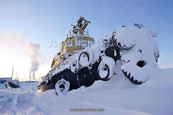 A tug boat frozen into the harbour at Tiksi during the winter. Northern Yakutia, Siberia, Russia.